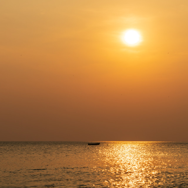 """""""Sunset in Costa Rica along pacific coast with single small boat on the ocean..."""" stock image"""