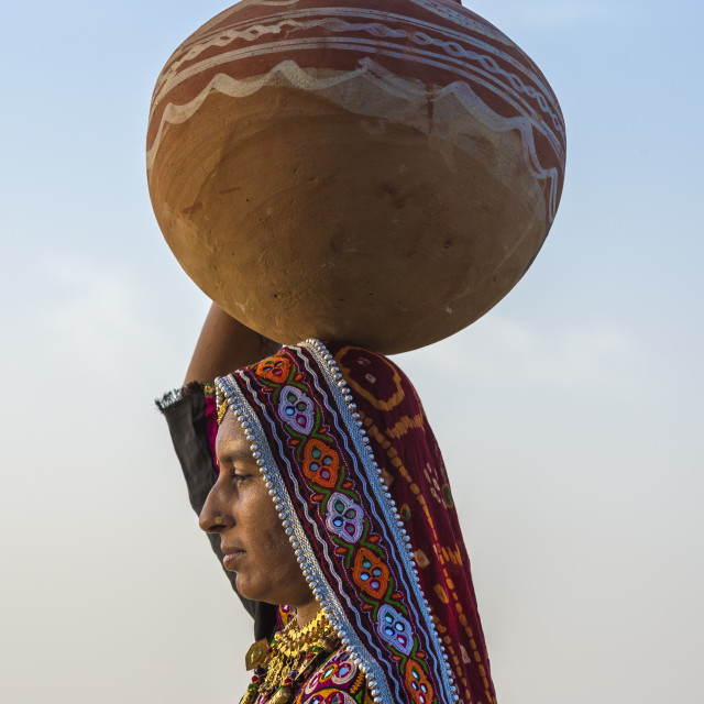 """""""Ahir Woman in traditional colorful cloth carrying water in a clay jug on her..."""" stock image"""