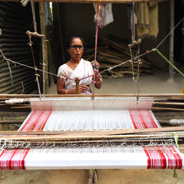 """""""Village woman with domestic handloom, weaving a traditional Assamese cotton..."""" stock image"""