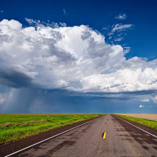 """Long straight road leading to a storm on the horizon"" stock image"