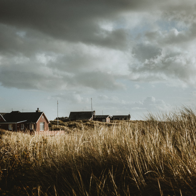 """Typical wooden holiday homes of Rømø island in Denmark during the autumn afternoon with the cloudy sky above them"" stock image"