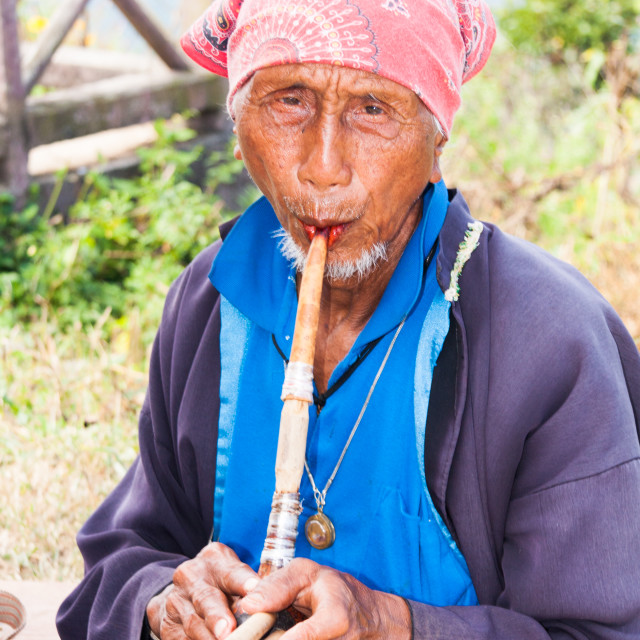 """""""Old Lahu hilltribe man playing a pipe in Mae Hong Son, Thailand"""" stock image"""