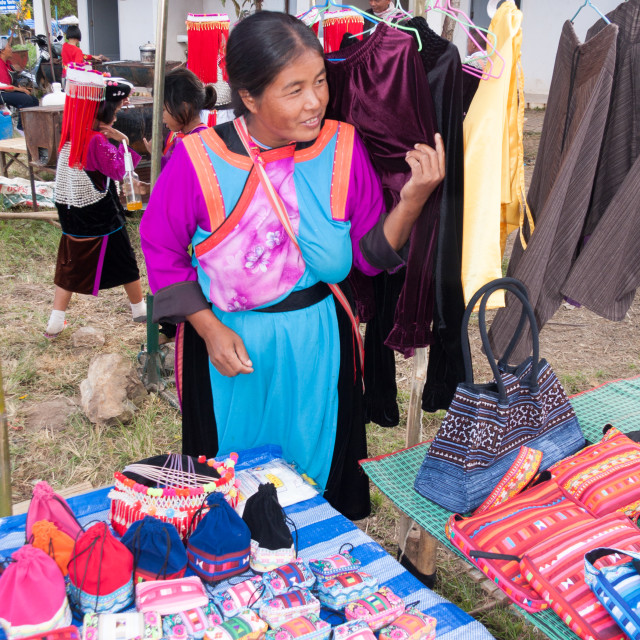 """""""Lisu hilltribe woman in traditional dress selling bags, hats and purses at a..."""" stock image"""