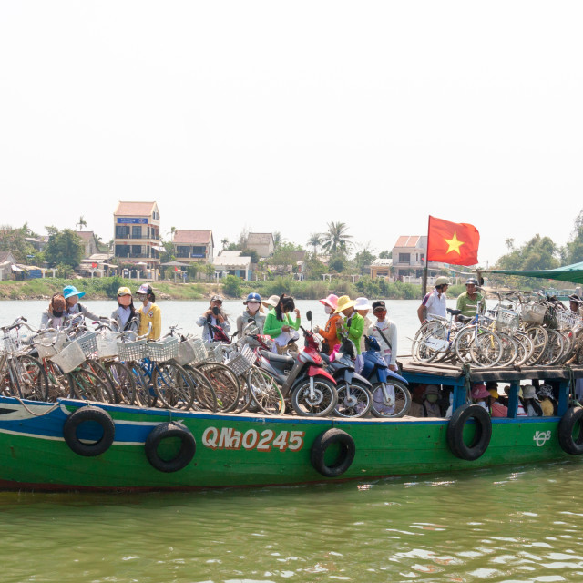 """""""Cyclists on the river ferry, Hoi An, Vietnam"""" stock image"""