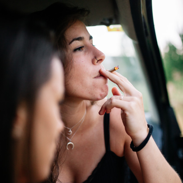 """""""Two young lesbians smoking inside a car"""" stock image"""