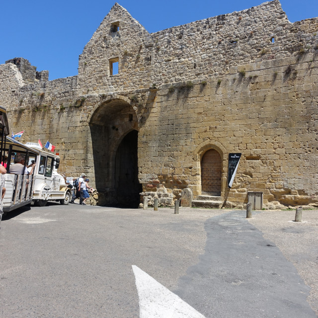 """""""Domme, France 15 july 2019: Tourists riding on the little tourist train about to pass through the Tower gate in the town of Domme in France"""" stock image"""