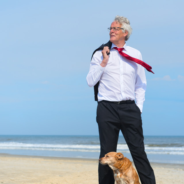 """Business man with dog at the beach"" stock image"
