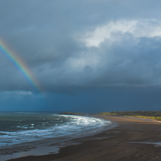 """Rainbow Over Rhossili Bay in Gower, Wales"" stock image"