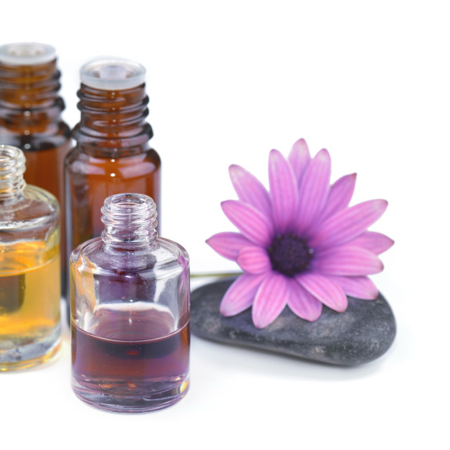 """essential oil bottles and flower on white background"" stock image"