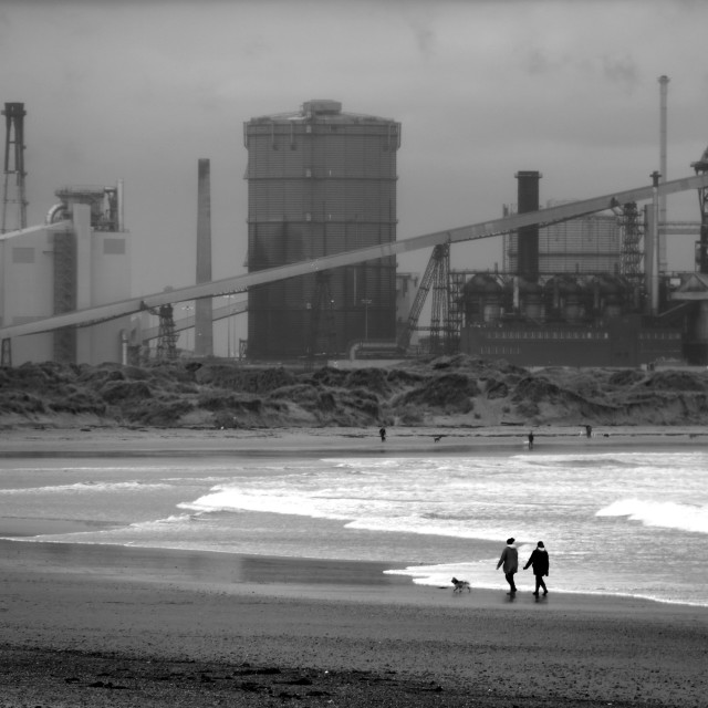 """""""Dog walkers in the shadow of Redcar's steelworks."""" stock image"""