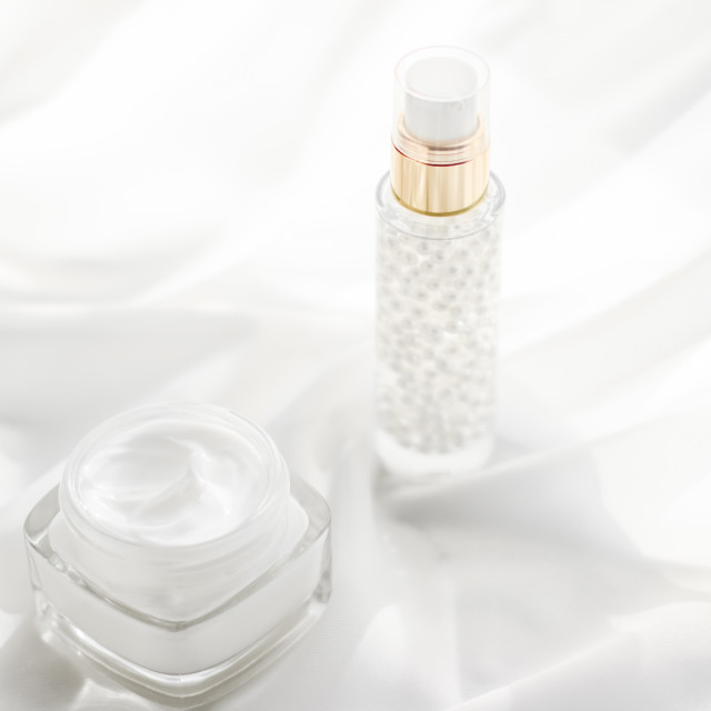 """Face cream moisturizer jar and serum gel on white silk, skin care lotion and..."" stock image"