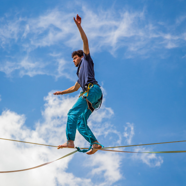 """Young slackliner man balancing on a slackline betweend two rocks. Highline..."" stock image"