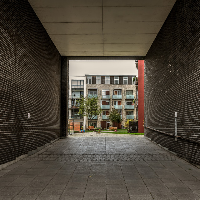 """""""Passage under a brick-building to a green garden with apartments"""" stock image"""