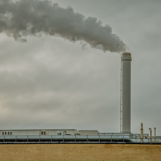 """""""Factory with a tall chimney with black smoke against the grey sk"""" stock image"""