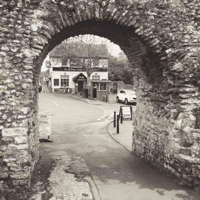 """""""Jaunted Pevensey castle and Pevesey High Street in Black and White"""" stock image"""