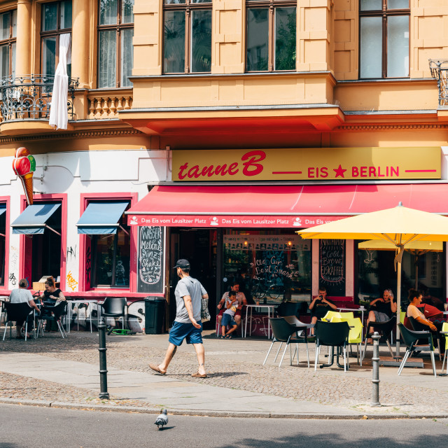 """Trendy restaurant with tables and umbrellas on sidewalk in Kreuzberg quarter."" stock image"