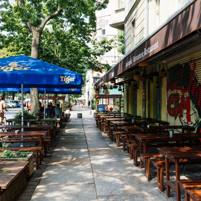 """Vietnamese restaurant with tables and umbrellas on sidewalk in Kreuzberg quarter."" stock image"