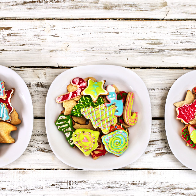 """Christmas gingerbread cookies on three plates by wooden table"" stock image"