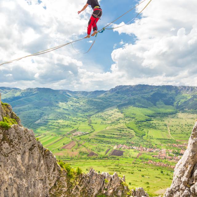 """""""Young slackliner man balancing on a slackline betweend two rocks. Highline..."""" stock image"""