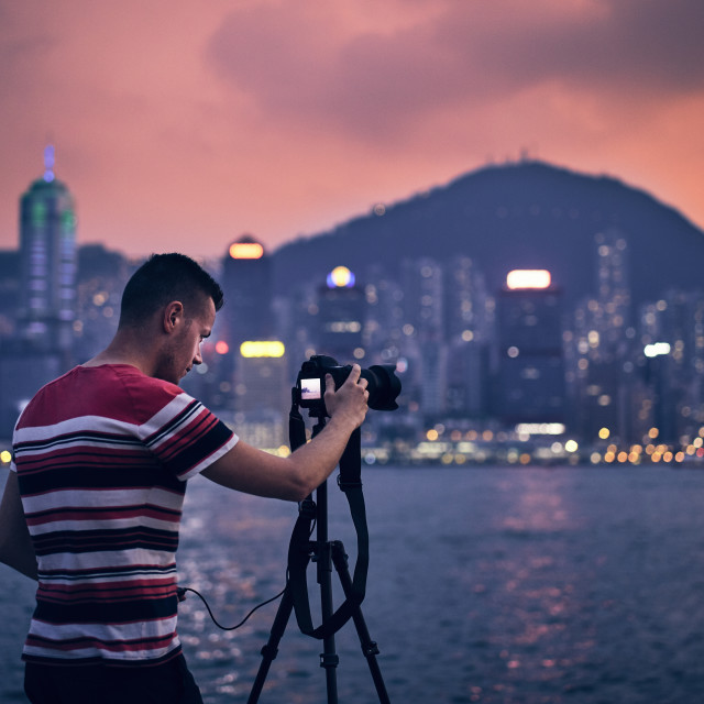 """Young man photographing urban skyline"" stock image"