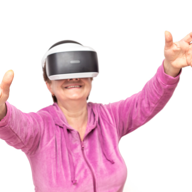 """senior woman with VR goggles enjoying virtual experience"" stock image"