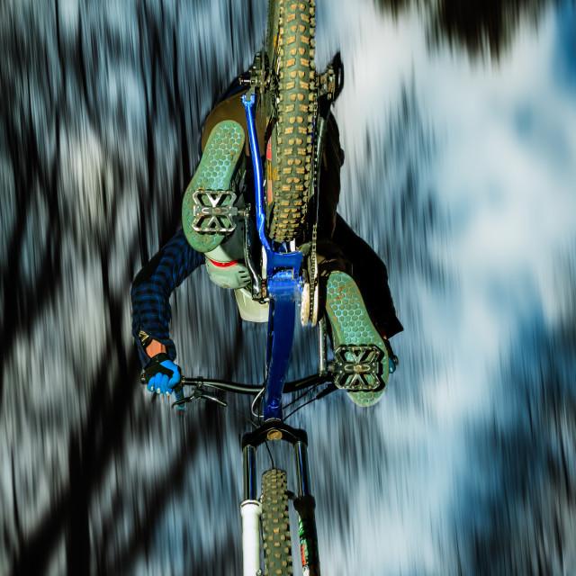 """Biker jumping seen from below"" stock image"