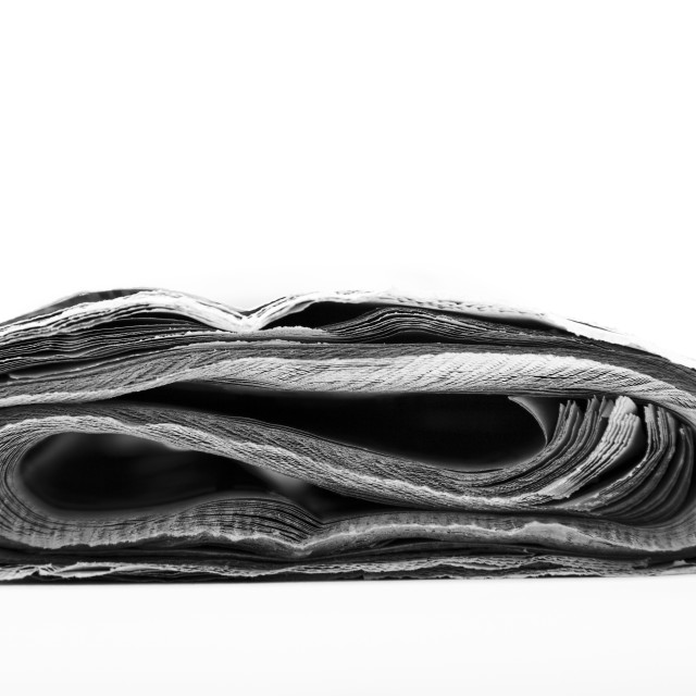 """Sideways view of a rolled up newspaper"" stock image"