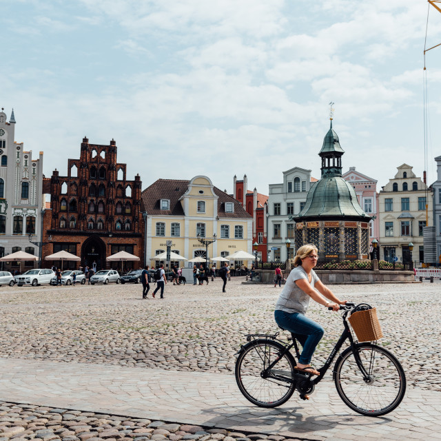 """""""Woman riding bicycle through square in historic centre of Wismar, Germany"""" stock image"""