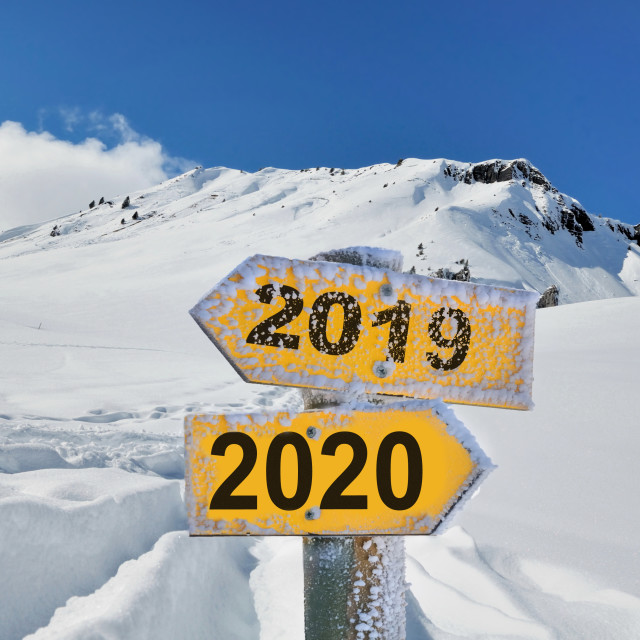 """yellow opposite direction panel 2019 and 2020 in front of snowy mountain landscape under blue sky"" stock image"