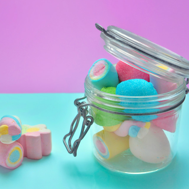 """colorful marshmallows in a glass jar on blue and pink background"" stock image"