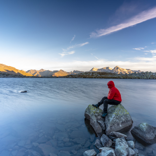 """Hiker sitting on rocks on water edge of Laghi Azzurri (Bergsee) at dawn,..."" stock image"