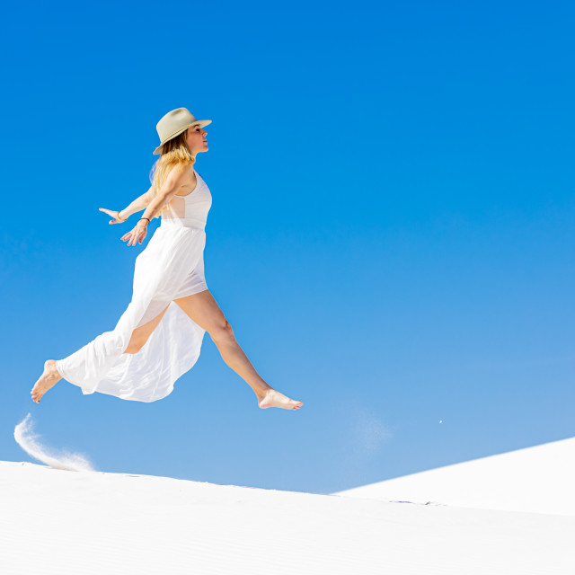 """""""Woman jumping on the Gypsum Sand Dune."""" stock image"""