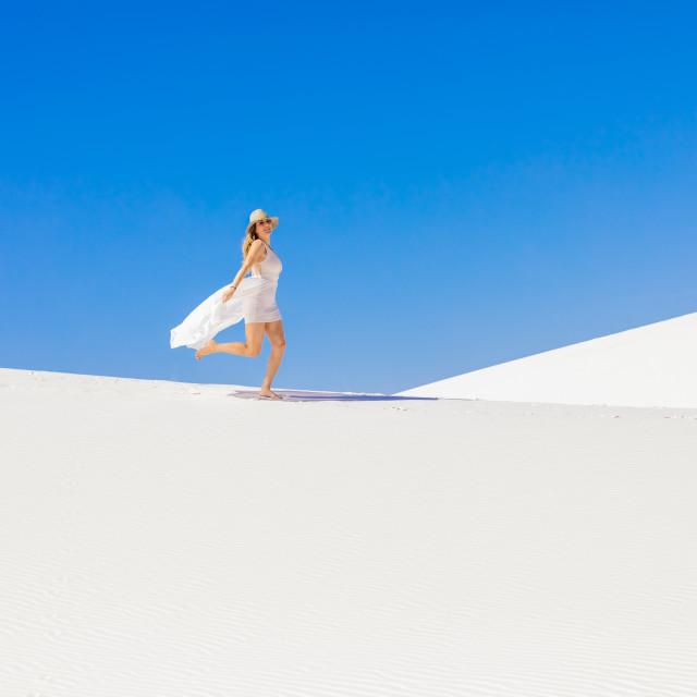 """""""Woman walking across Gypsum Sand Dune."""" stock image"""