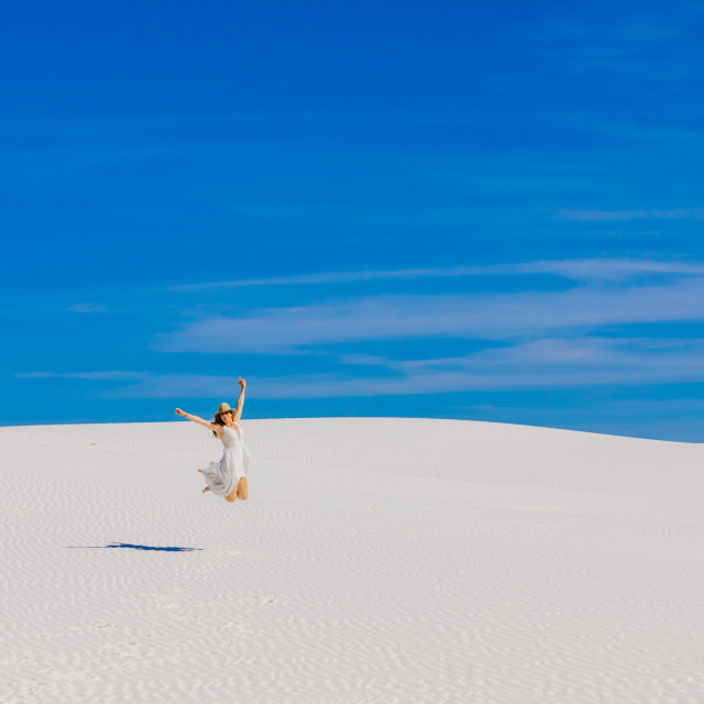 """Woman jumping on Gypsum Sand Dune."" stock image"
