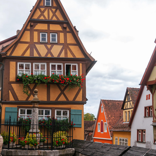 """German wood framed houses and little fenced fountain"" stock image"