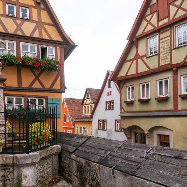 """German wood framed houses and little fenced fountain at Plonlei"" stock image"
