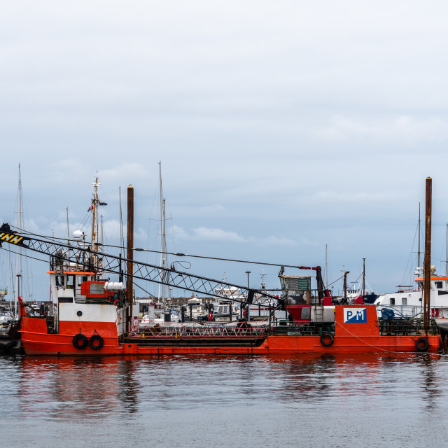 """Red dredge ship moored in the harbour of Sassnitz in Rugen Island"" stock image"