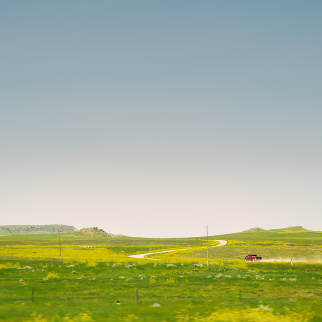 """""""A moving red truck throwing dust travelling along a curving gravel road through a yellow meadow dotted with mountains in a summer sunny landscape"""" stock image"""