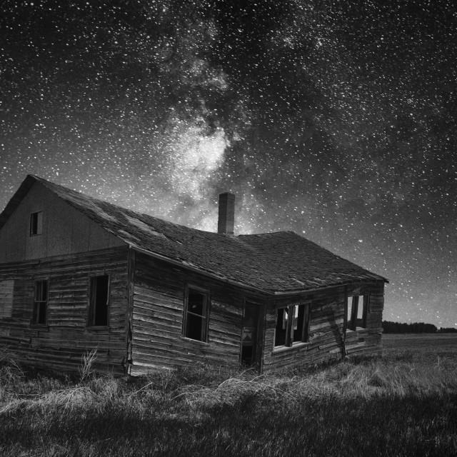 """""""An old weathered and faded clapboard farmhouse sagging in the middle under a starry night sky in a black and white countryside nighttime landscape"""" stock image"""