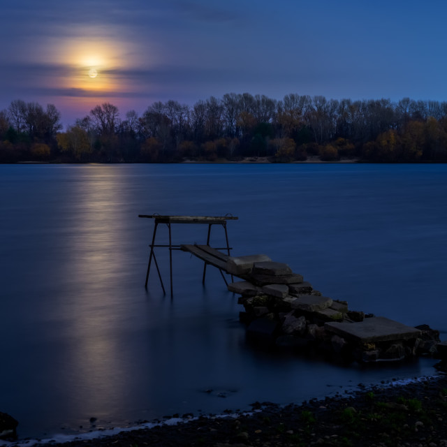 """""""Real full moon over the autumn forest close to Dnieper river in Kiev, Ukraine. Soft clouds in the dark sky cover partially our natural satellite. A pontoon in the foreground. The water looks like a glossy blue mirror."""" stock image"""