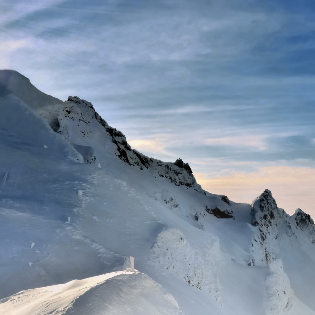 """sunlight on little silouettes of hikers climbing a snowy mountain"" stock image"