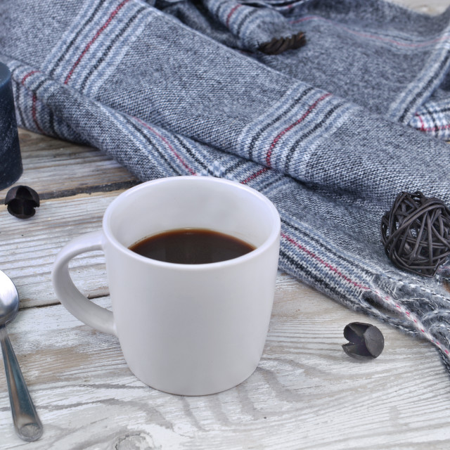 """mug of coffee with scarf and candle on a table"" stock image"