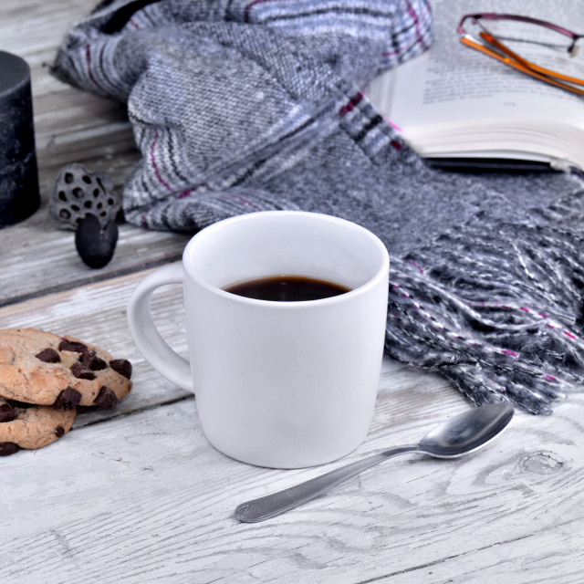 """mug of coffee withscarf and candle on a white table"" stock image"