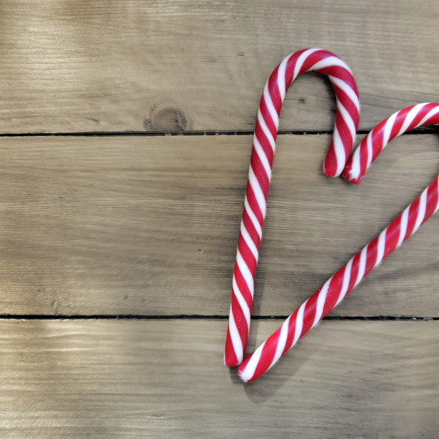 """candy canes forming a heart on wooden background"" stock image"