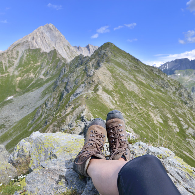 """foot and legs of a hiker sitting at the top of alpine mountain"" stock image"