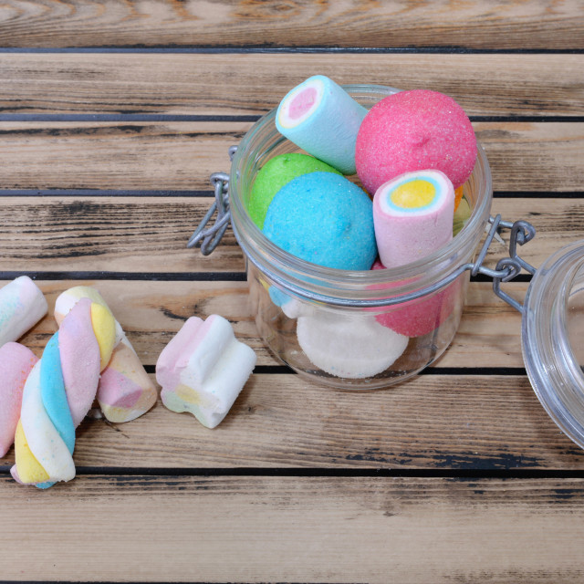 """colorful marshmallow in a glass jar on a rustic wooden table"" stock image"