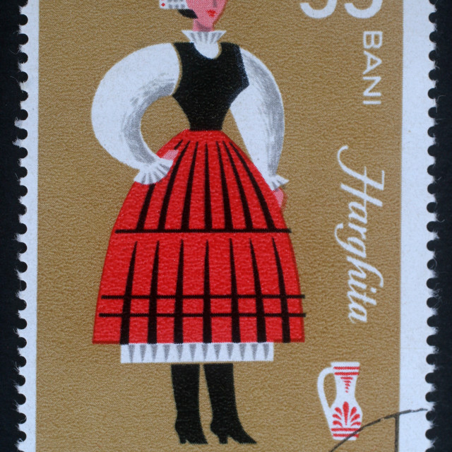 """Stamp printed in Romania shows image of a Harghita woman, from the regional costumes series, circa 1973."" stock image"