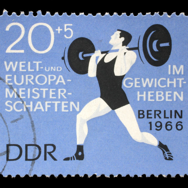 """Stamp printed in GDR (German Democratic Republic - East Germany) shows weightlifter, circa 1966."" stock image"
