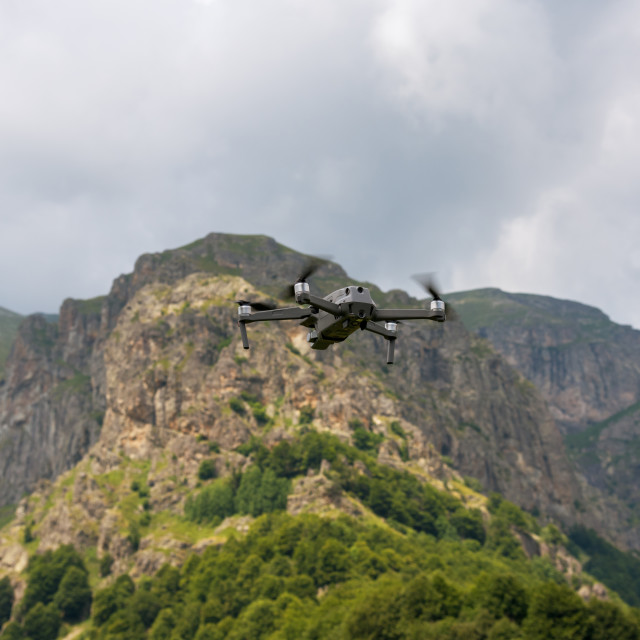 """""""Drone with camera flying over mountain fields."""" stock image"""