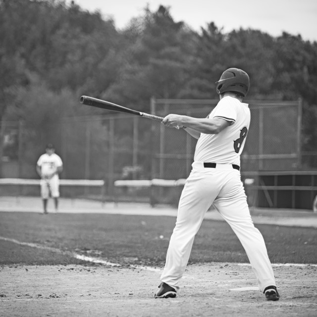 """""""The backside of a eighteen year old male in a baseball uniform and helmet swinging the bat at a pitch in a black and white summer landscape"""" stock image"""